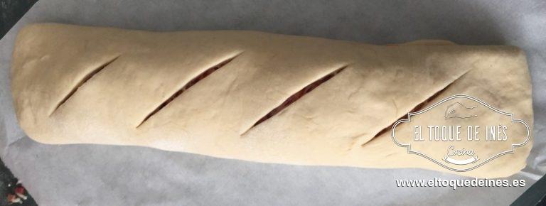 Ponemos el pan en la bandeja del horno cubierta con papel de hornear. Decoramos la superficie haciendo unas marcas profundas,yo uso un bisturí,pero sirve con un cuchillo bien afilado.