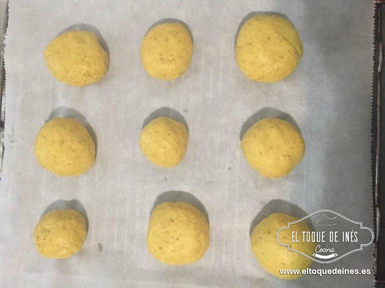 Cada porción la boleamos para que nos quede sin fisuras y vamos colocando encima de papel de hornear sobre la bandeja del horno que vayamos a usar.