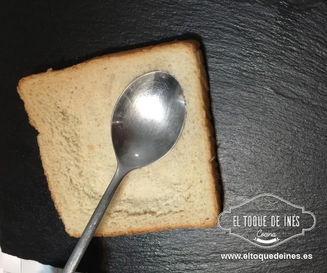 Aplastamos el interior de cada rebanada de pan de molde, sin tocar a los bordes; nos podemos ayudar de una cuchara.