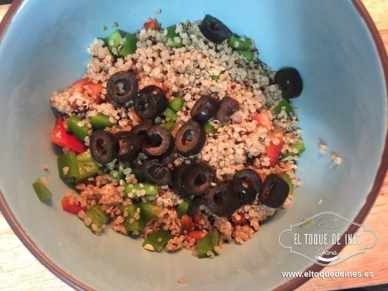 En un bol mezclamos la quinoa con los pimientos y los aros de aceitunas negras.