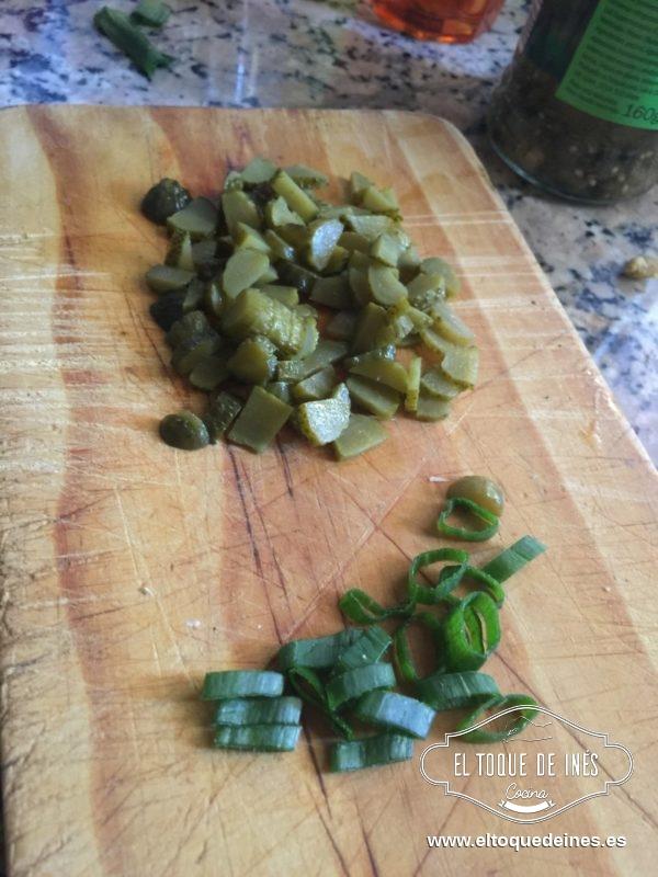Mientras picamos los pepinillos  la cebolleta, bien picado todo.