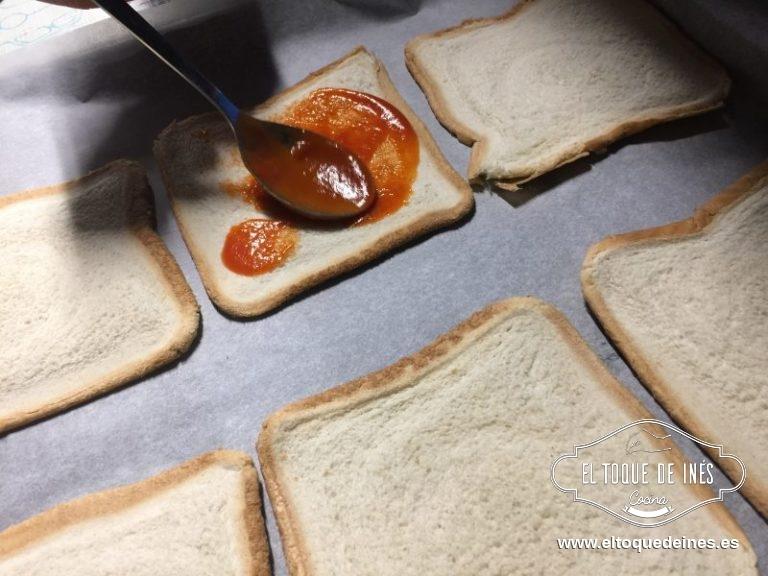 Colocamos sobre papel de horno, echando una cucharada de tomate frito sobre cada una de las 4 rebanadas.