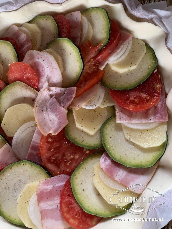 Vamos colocando superponiendo un poco una rodaja de calabacín, patata, cebolla, bacon y tomate.