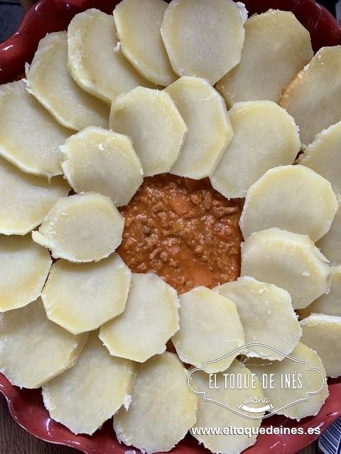 En una fuente de horno echamos la carne que ya tenemos preparada y encima vamos situando las patatas que se superpongan un poco unas encima de otras.